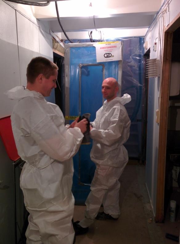 Arbeiderne gjør seg klare for en ny runde med asbestfjerning. Luftslusen i bakgrunnen.